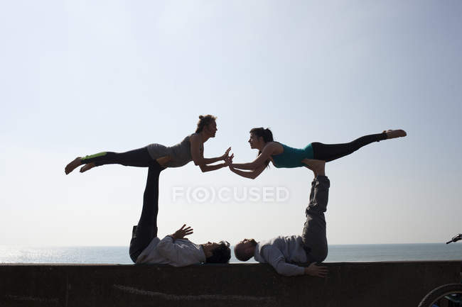 Symmetrical silhouetted men and women practicing acrobatic yoga on wall at Brighton beach — Stock Photo