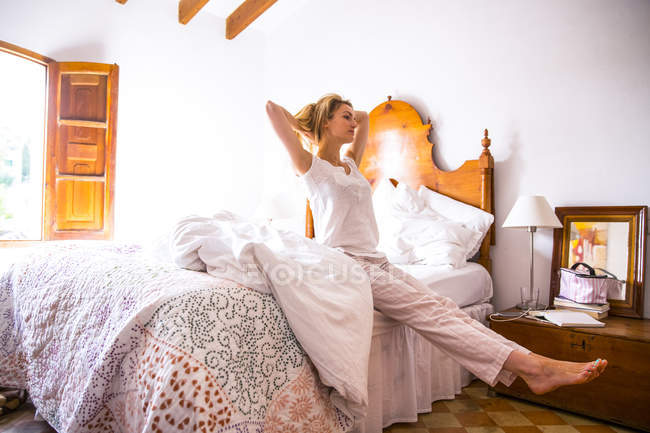 Junge Frau, die Dehnung auf Bett morgens — Stockfoto