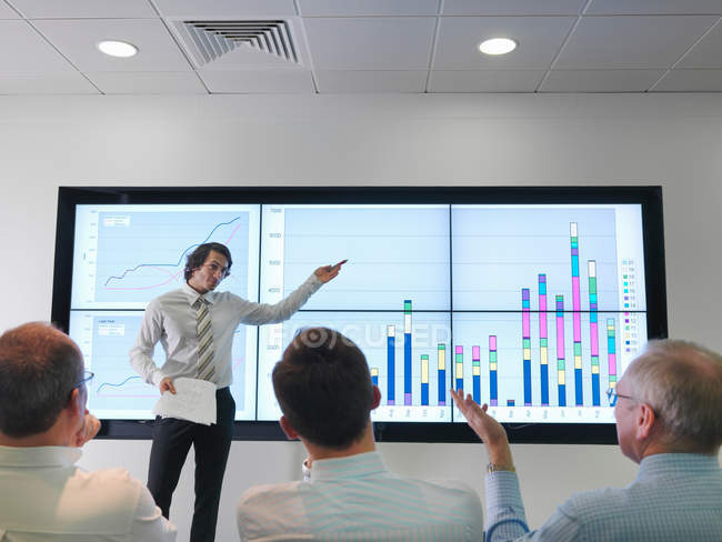 Business meeting with graphs on screen — Stock Photo