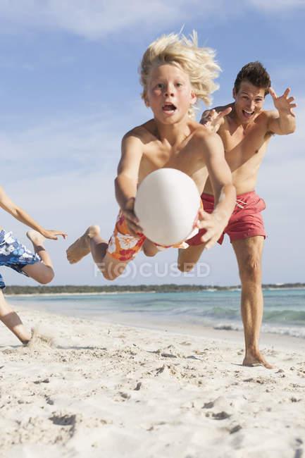 Ragazzo che salta a mezz'aria con pallone da rugby inseguito da fratello e padre sulla spiaggia, Maiorca, Spagna — Foto stock