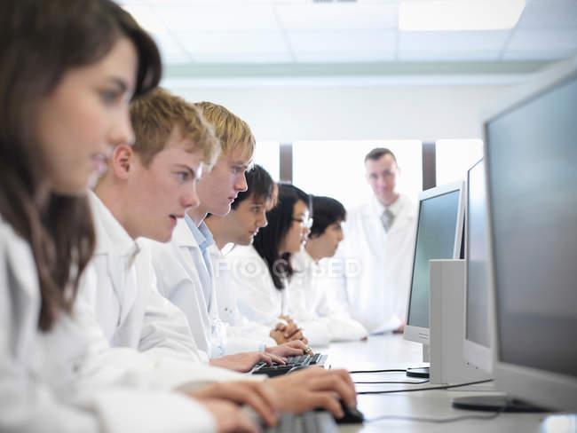 Научные студенты, работающие на компьютерах в школьной лаборатории — стоковое фото