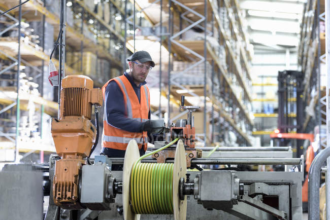 Worker winding electrical cables at cable storage facility — Stock Photo