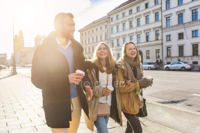 Молодой человек и подруги прогуливаются с кофе на вынос на городской улице — стоковое фото