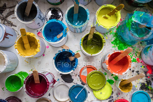 Overhead view of stirrers in paint pots in surfboard maker workshop — Stock Photo