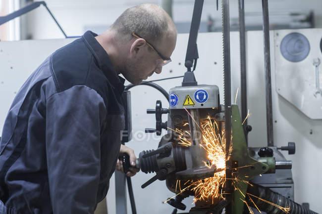 Kaukasischer Erwachsener überwacht Schleifmaschine in Werkstatt — Stockfoto