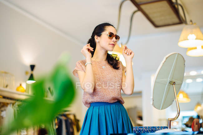 Young woman trying on sunglasses in boutique — Stock Photo