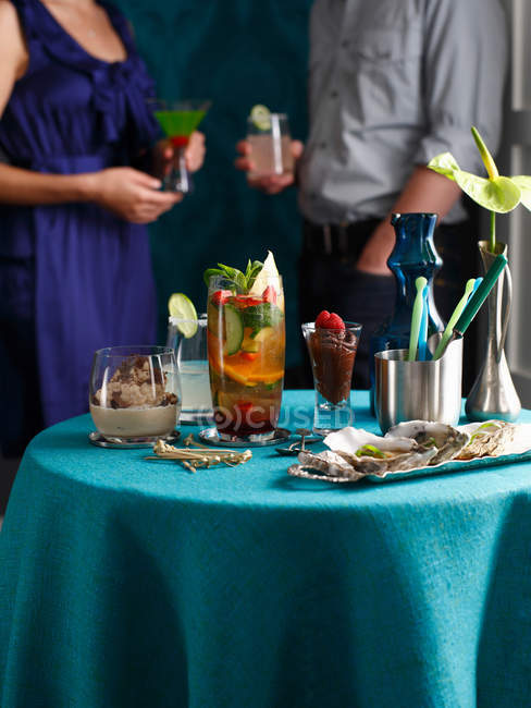Table with oysters, cocktail drinks and desserts at party — Stock Photo