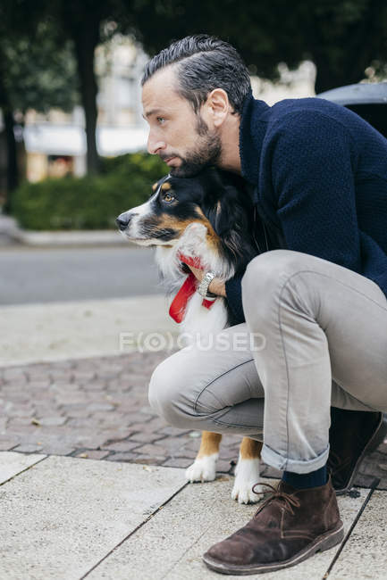 Mid adult man crouching with pet dog on city sidewalk — Stock Photo