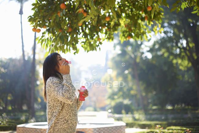 Вид сбоку зрелой женщины, надувающей пузыри под апельсиновым деревом, Севилл, Испания — стоковое фото