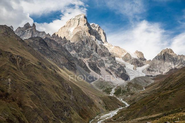 Valley and rocky mountains under blue cloudy sky — Stock Photo