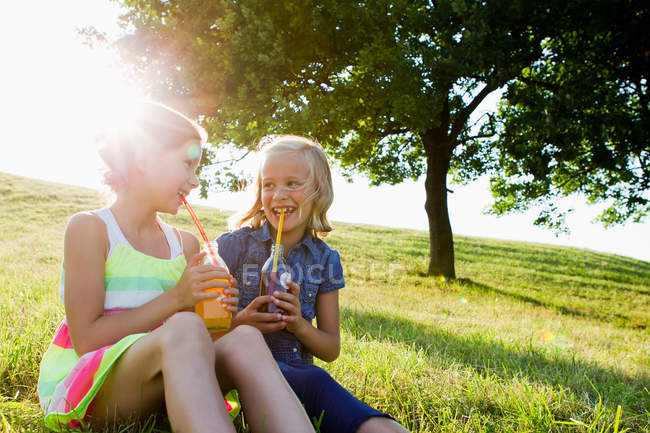 Laughing girls drinking juice outdoors — Stock Photo