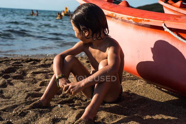 Мальчик сидит на пляже на лодке, глядя — стоковое фото