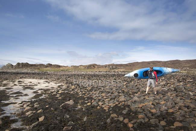 Mid adult man carrying canoe, Loch Eishort, Isle of Skye, Hebrides, Scotland — Stock Photo