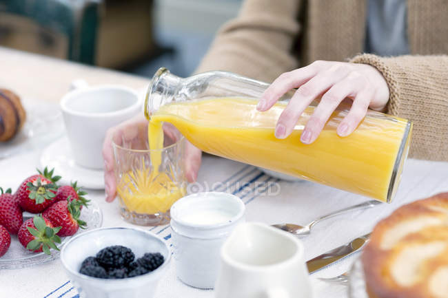 Cropped view of female hands pouring orange juice from bottle in glass — Stock Photo