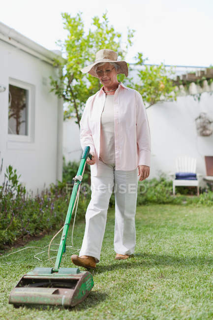 Young Pregnant Woman Mowing The Lawn With Manual Lawn