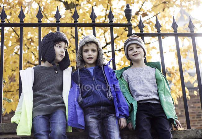 Три мальчика на улице, прислонившиеся к забору, вид с низкого угла — стоковое фото