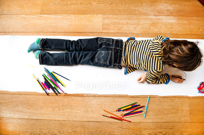 Overhead view of boy lying on top of and drawing on long paper — Stock Photo