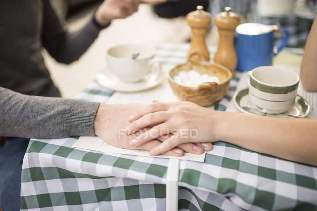 Ausgeschnittene Ansicht eines Paares, das sich an einem Café-Tisch an den Händen hält — Stockfoto