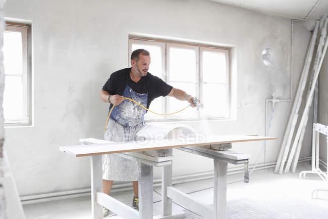 Hombre spray pintura madera en interiores - foto de stock