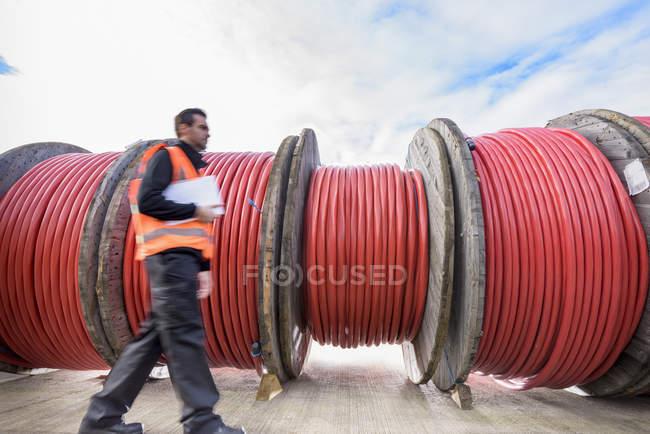 Рабочий, проходящий мимо катушек электрического кабеля в хранилище кабелей — стоковое фото