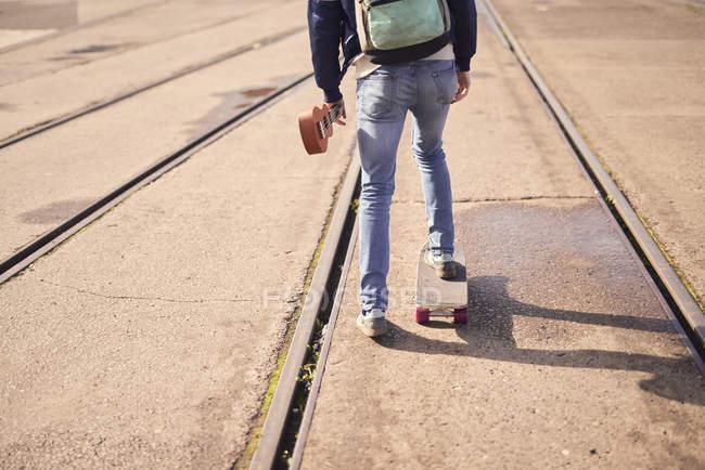 Jeune homme Skate entre les lignes de tramways, vue arrière, faible section — Photo de stock
