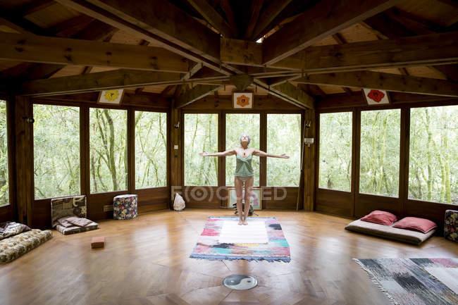 Femme en position d'yoga dans la maison en bois — Photo de stock