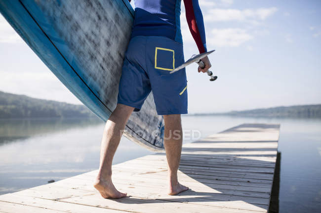 Waist down view of young man carrying paddleboard along pier, lake Pilsensee, Germany — Stock Photo