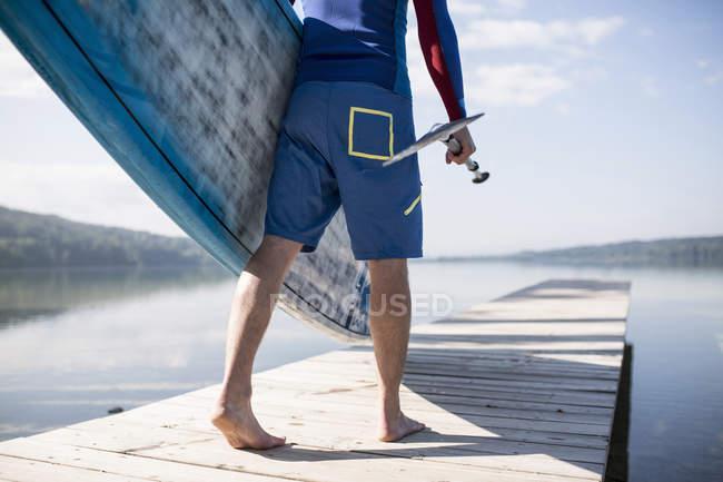 Vita in giù vista del giovane che trasporta paddleboard lungo molo, lago Pilsensee, Germania — Foto stock