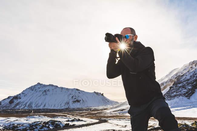 Man photographing view, Arnarstapi. Iceland — Stock Photo
