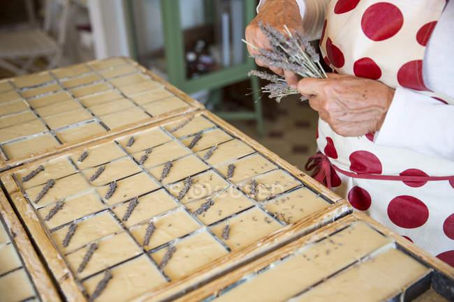 Section médiane de femme appliquant lavande séchée à barres dans l'atelier de savon artisanal de savon — Photo de stock
