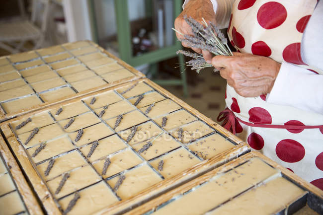 Mid section of woman applying dried lavender to soap bars in handmade soap workshop — Stock Photo