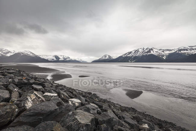 Snowcapped mountains and lake under cloudy sky — Stock Photo