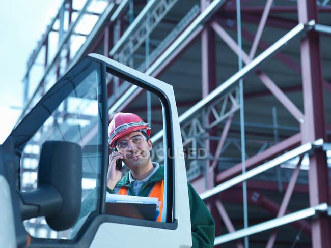 Workman utilisant le téléphone mobile par van et le cadre de construction en acier sur le chantier — Photo de stock
