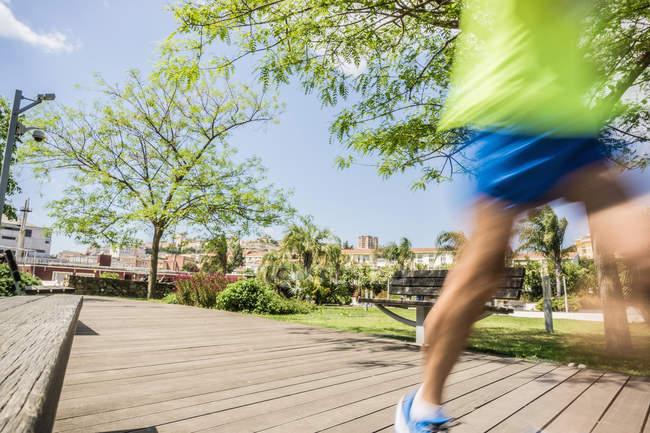 Розмиті руху бігун працює на парк boardwalk — стокове фото