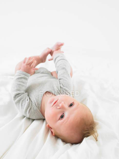 Портрет маленького ребенка, лежащего на спине — стоковое фото