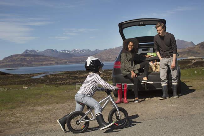 Parents watching son ride bike, Loch Eishort, Isle of Skye, Hebrides, Scotland — Stock Photo
