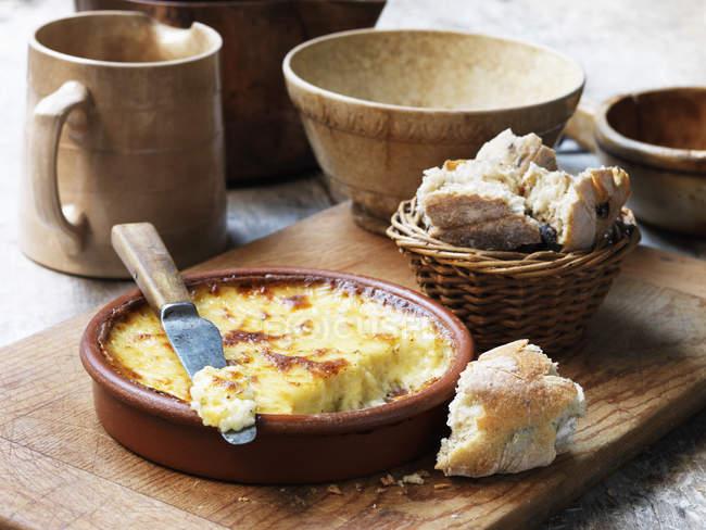 Formaggio cotto in piatto di terracotta con pane e coltello — Foto stock