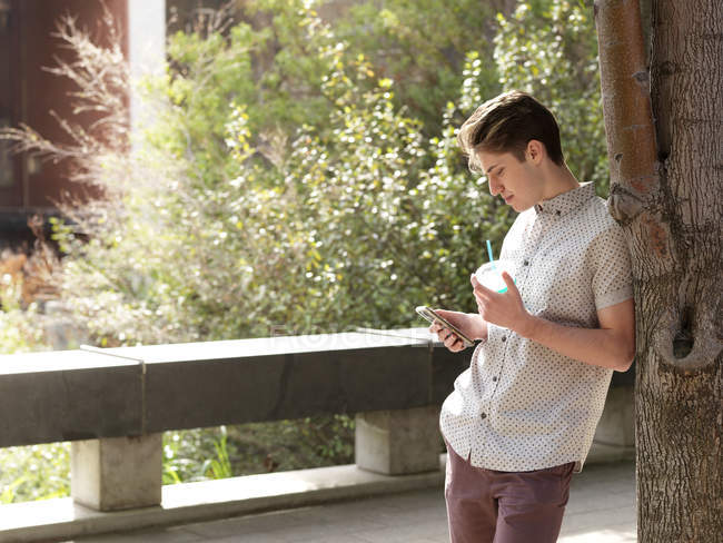 Young man outdoors, leaning against tree, using smart phone, holding takeaway cup — Stock Photo