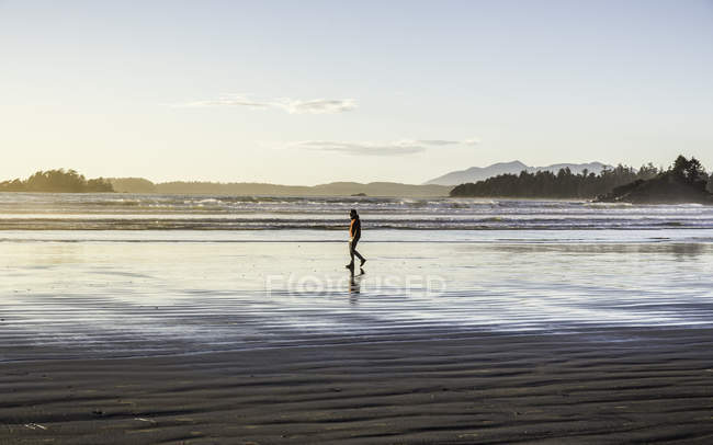Man strolling on Long Beach at sunrise, Pacific Rim National Park, Vancouver Island, British Columbia, Canada — Stock Photo