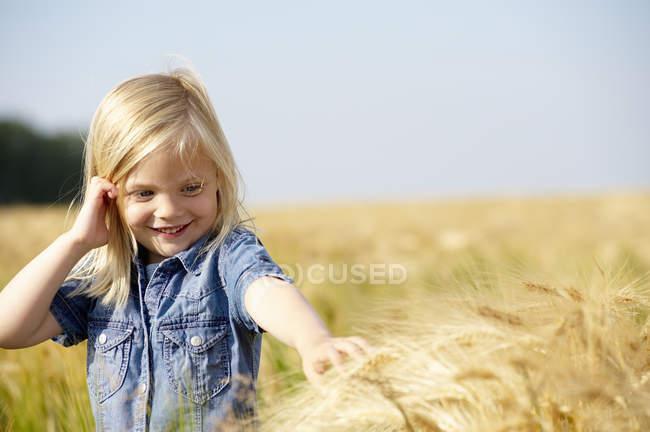 Fille caressant le blé dans un champ — Photo de stock