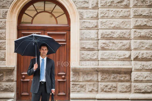 Homme d'affaires portant un parapluie dans la rue — Photo de stock