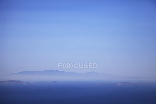 Seascape and distant misty view of Andros Island from Tinos Island, Greece — Stock Photo