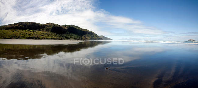 Sky and mountain reflected in water — Stock Photo