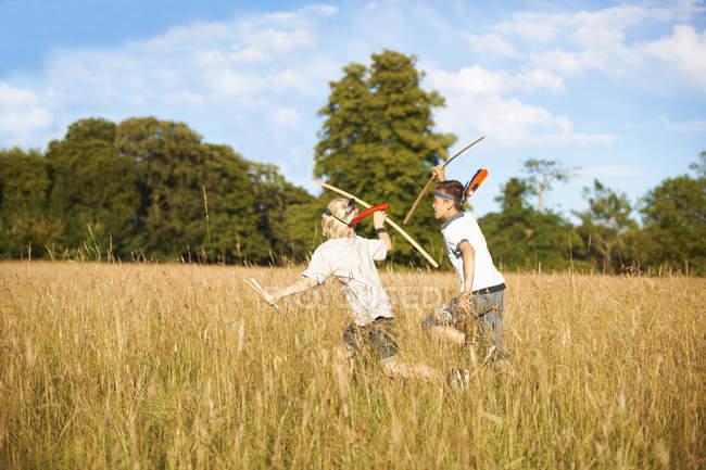 Два маленьких хлопчиків, що працюють з лука і стріли — стокове фото