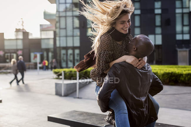 Happy blonde caucasian woman and African ethnicity man in street, couple in love laughing and hugging — Stock Photo
