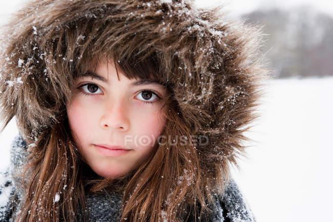 Девушка в меховой шапке смотрит в камеру — стоковое фото