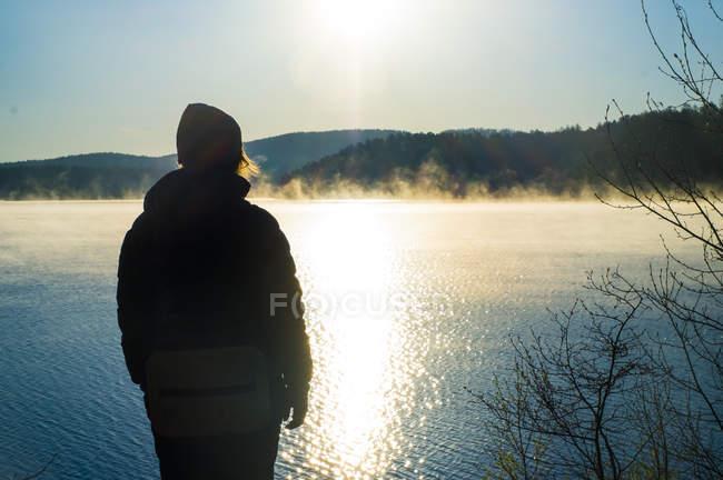 Tourist enjoying view by lake at sunset — Stock Photo