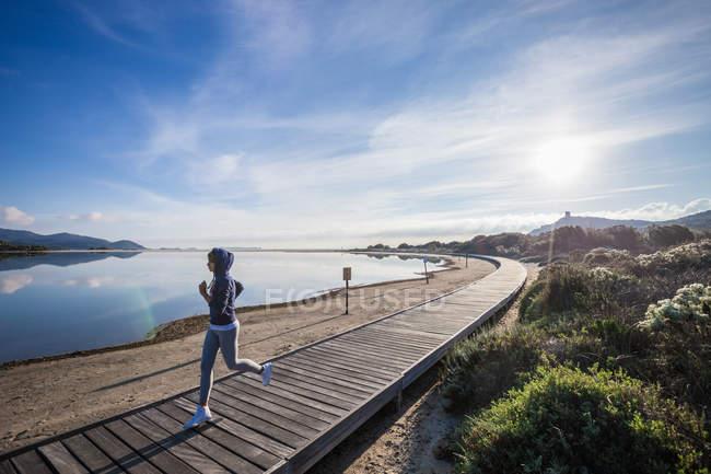 Corredor feminino jovem correndo no calçadão da praia, Villasimius, Sardenha, Itália — Fotografia de Stock