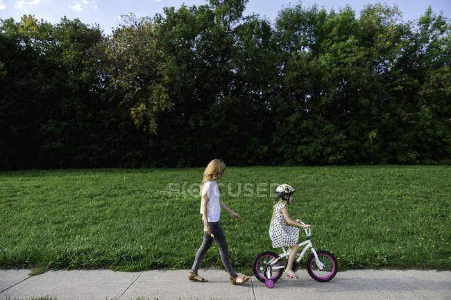 Young girl riding her bicycle followed by mother — Stock Photo