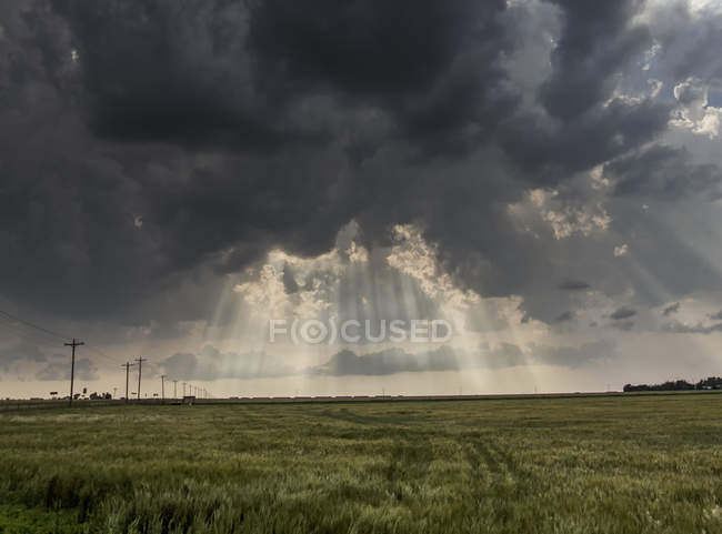 Crepuscular rays shining through clouds over country landscape following passage of a severe thunderstorm — Stock Photo